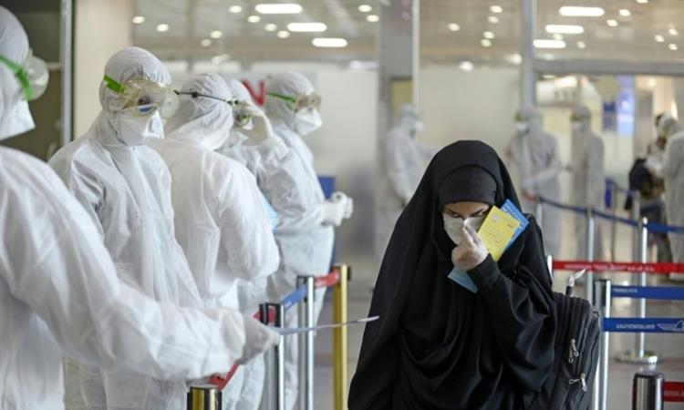 Nhân viên y tế phát tờ thông tin phòng dịch cho hành khách đến từ Iran tại sân bay Najaf ở Iraq ngày 5/3. Ảnh: AFP.