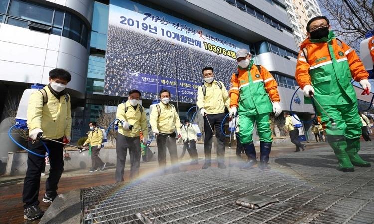 Quan chức chính phủ Hàn Quốc phun thuốc khử trùngtrước chi nhánh nhà thờ Tân Thiên Địaở Daegu hôm 6/3. Ảnh: AFP.