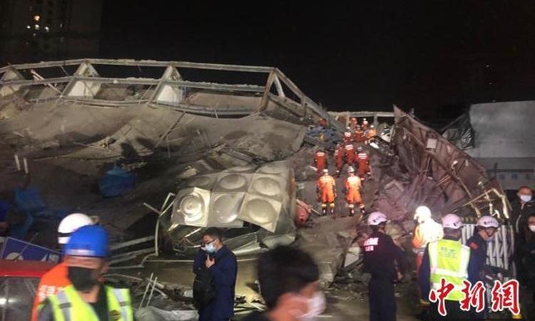 Lực lượng cứu hộ làm việc tại hiện trường sập khách sạn Xinjia. Ảnh: Chinanews.