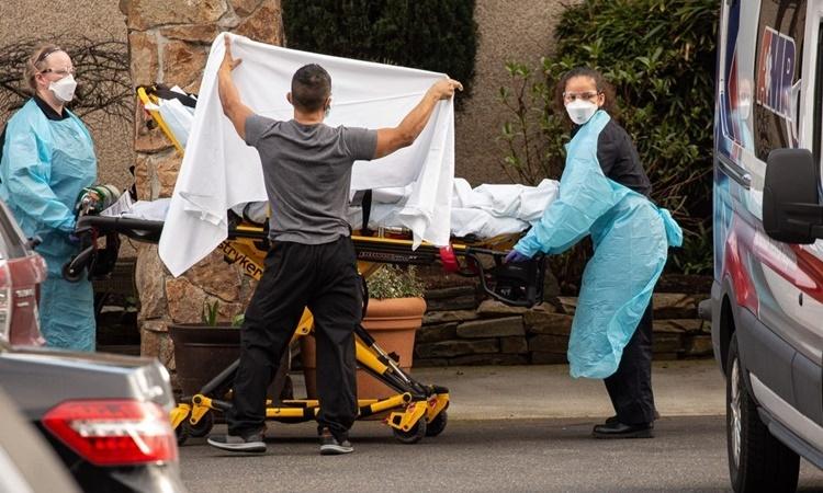 Nhân viên y tế di chuyển một bệnh nhân nghi nhiễm nCoV lên xe cứu thương ở Kirkland, Mỹ, ngày 29/2. Ảnh: AFP.
