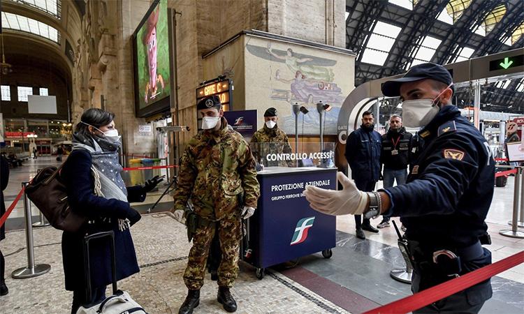 Cảnh sát và binh sĩ Italy kiểm tra hành khách lên tàu rời Milan ngày 9/3. Ảnh: AP.