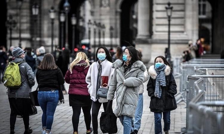Khách du lịch đi bộ gần kim tự tháp kính Lourve ở Paris ngày 28/2. Ảnh: AFP.