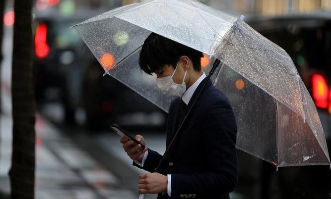M?t ng??i ?i trên ???ng ph? t?i Tokyo ngày 10/3. ?nh: Reuters.
