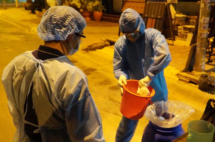 Nhân viên y tế phun thuốc khử trùng khu vực nhà bệnh nhân 34 ở TP Phan Thiết, tối 10/3. Ảnh: Việt Quốc.