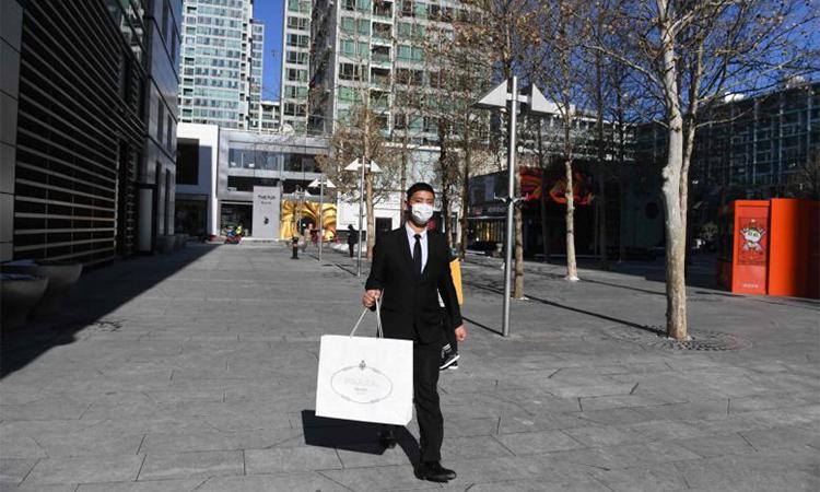 Người đàn ông đeo khẩu trang phía trước một trung tâm thương mại sang trọng ở Bắc Kinh, Trung Quốc hom 8/2. Ảnh: AFP.