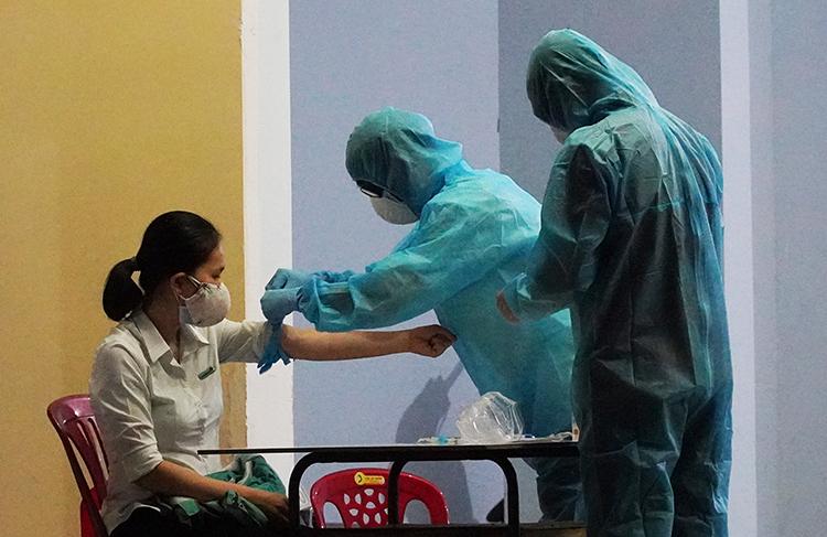 Nhân viên y tế Bình Thuận lấy mẫu máu xét nghiệm những ngườitiếp xúc với 4 ca nhiễm nCoV tại Phan Thiết, tối 11/3. Ảnh: Việt Quốc.