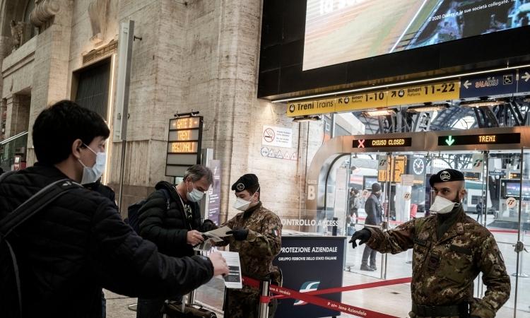 Lực lượng an ninh kiểm tra hành khách lên tàu rời Milan, Italy, ngày 9/3. Ảnh: New York Times.