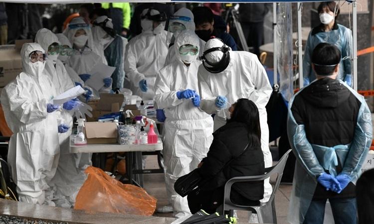 Nhân viên y tế lấy mẫu từ các nhân viên tại một tòa nhà, nơi có 46 người làm cùng văn phòng nhiễm nCoV, ở tây nam Seoul hôm 10/3. Ảnh: AFP.