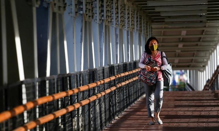 Người phụ nữ đeo khẩu trang bảo hộ đi trên một cây cầu ở thủ đô Jakarta,Indonesia hôm 9/3. Ảnh: Reuters.