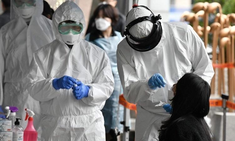 Nhân viên y tế Hàn Quốc lấy mẫu xét nghiệm nCoV cho một phụ nữ ở Seoul ngày 10/3. Ảnh: AFP.