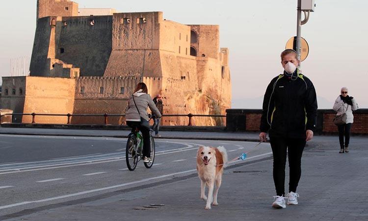 Một phụ nữ đeo khẩu trang, dắt chó đi dạo ở Naples, Italy hôm 11/3. Ảnh: Reuters.