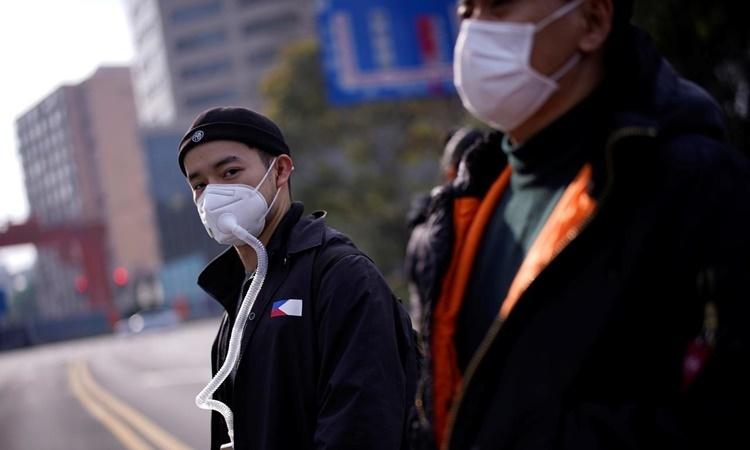 Người dân đeo khẩu trang khi ra đường tại Thượng Hải, Trung Quốc, ngày 10/3. Ảnh: Reuters.