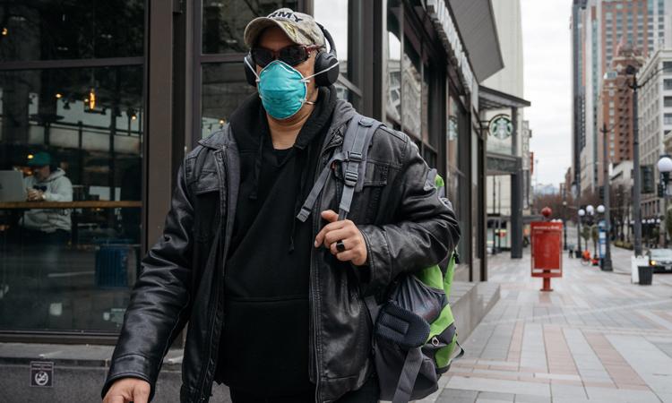 Người đàn ông đeo khẩu trang đi trên phố vắng bóng người ở Seattle, bang Washington. Ảnh: NY Times.