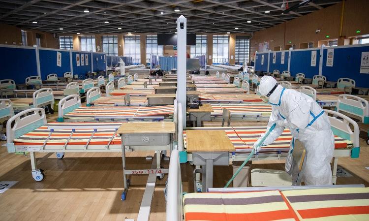 Bác sĩ dọn dẹp một bệnh viện dã chiến ở Vũ Hán hôm 10/3 sau khi toàn bộ bệnh nhân xuất viện. Ảnh: AFP.