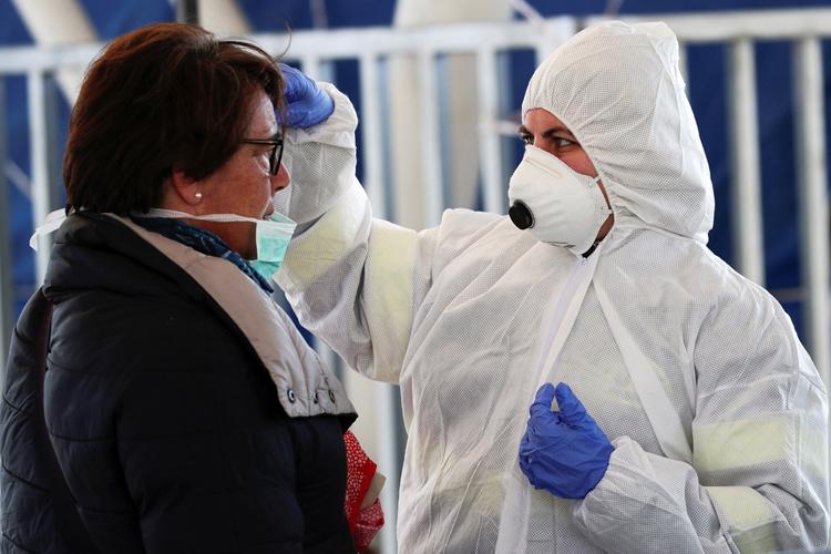 Một người dân được đo thân nhiệt tại Naples, Italy hôm 10/3. Ảnh: Reuters.
