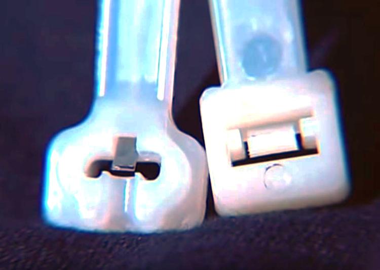 Còng rút cảnh sát (trái) có chốt inox, khác chốt nhựa của loại dây rút thường. Ảnh: Filmrise.