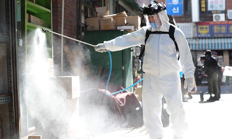 Nhân viên y tế phun hóa chất khử trùng để ngăn Covid-19 tại Soeul, Hàn Quốc ngày 11/3. Ảnh: AFP.