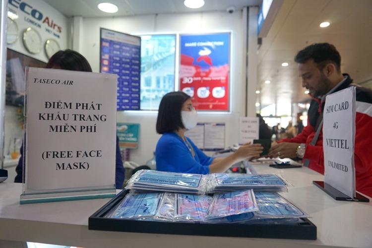 Một số đơn vị phát khẩu trang miễn phí ở sân bay Nội Bài. Ảnh: Gia Chính.