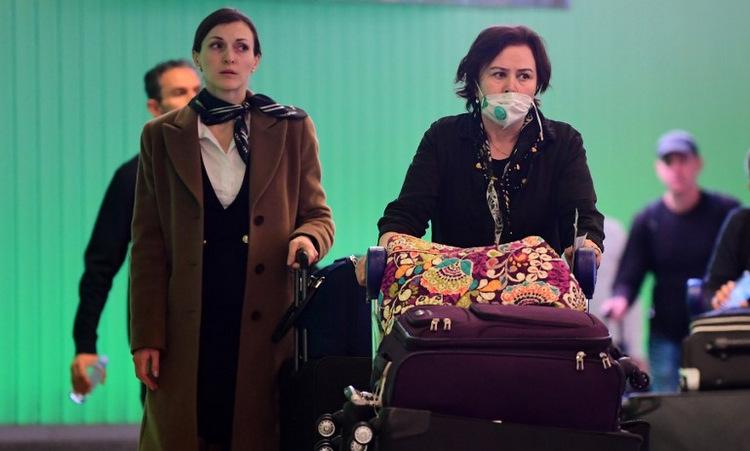 Hành khách đáp xuống sân bay quốc tế Los Angeles hôm 12/3. Ảnh: AFP.