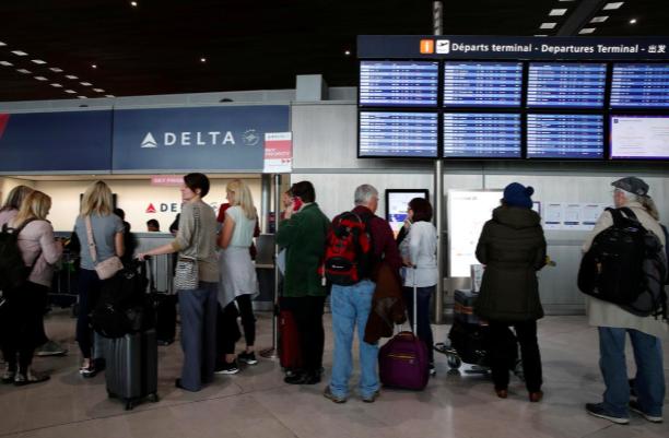 Hành khách xếp hàng trước quầy vé của hãng Delta tại sân bay quốc tế Charles de Gaulle, Paris, Pháp hôm 12/3. Ảnh: Reuters