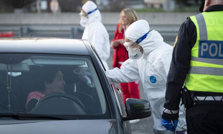 Nhân viên y tế Italy kiểm tra thân nhiệt một tài xế gần biên giới với Slovenia hôm 11/3. Ảnh: AFP.