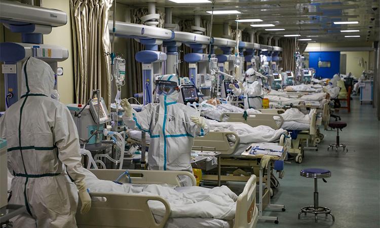 Nhân viên y tế mặc đồ bảo hộ, điều trị cho các bệnh nhân Covid-19 tại một bệnh viện dã chiến ở Vũ Hán, tỉnh Hồ Bắc, Trung Quốc hôm 6/2. Ảnh: Reuters.