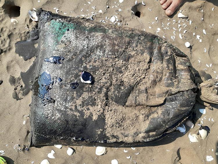 Một số bao chứa đã bị rách, chất lỏng đặc sệt màu đen tràn ra ngoài có mùi hôi như dầu. Ảnh: An Nam
