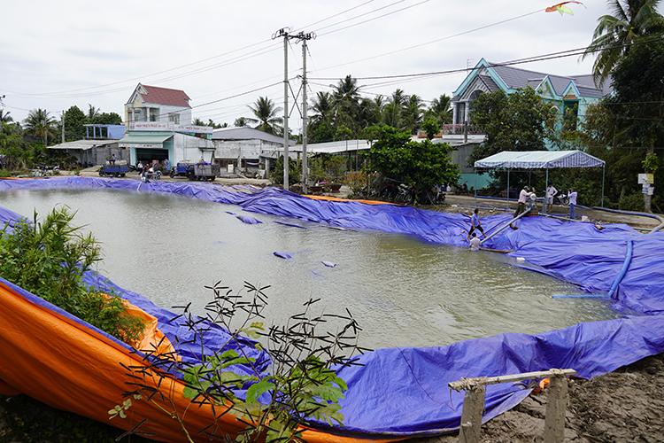 Ao dã chiến chứa gần 1.000 mét khối nước, được bơm từ sà lan để hỗ trợ người dân tưới sầu riêng. Ảnh: Hoàng Nam