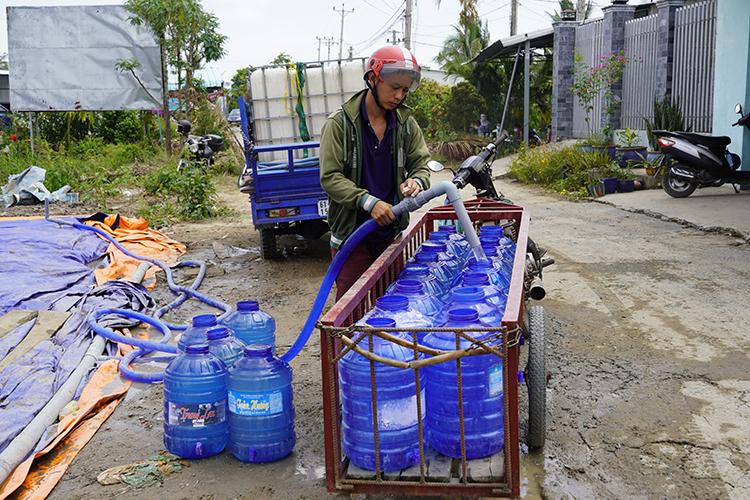 Người dân tận dụng xe kéo tự chế, lấy nước miễn phí từ ao dã chiến vào các thùng về tưới cây. Ảnh: Hoàng Nam