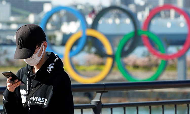 Du khách đeo khẩu trang bên biểu tượng của Thế vận hội mùa hè 2020 ở Tokyo, Nhật Bản hôm 3/3. Ảnh: AP.