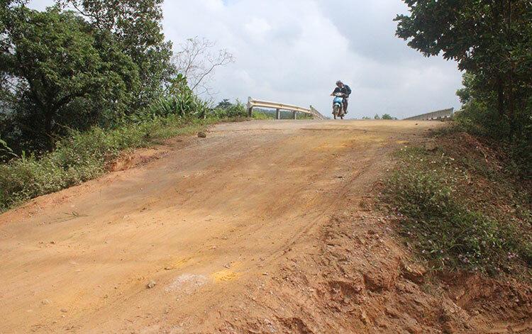 Hai đầu cầu chưa thể làm đường nhựa đấu nối, nhà chức trách phải đổ đất làm đường để người dân đi tạm. Ảnh: Đức Hùng