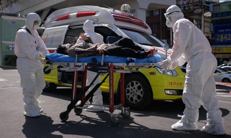 Nhân viên y tế đưa một bệnh nhân vào nhập viện tại Daegu hôm 12/3. Ảnh: AFP.