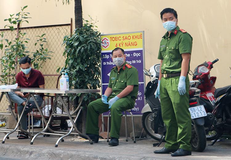 Cảnh sát và ngành y tế giám sát, hạn chế người dân ra vào chung cư Hoà Bình chiều 15/3. Ảnh: Hà An.