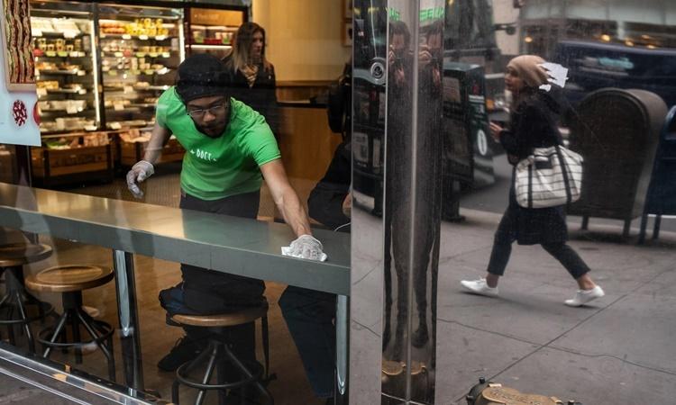 Nhân viên tại một cửa hàng bánh sandwich ở Manhattan, New York, lau chùi bàn cho khách. Ảnh: NYTimes.