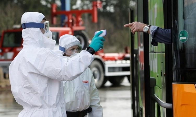 Cảnh sát kiểm tra nhiệt độ một chiếc xe buýt tại trạm kiểm soát biên giới Czech - Đức ngày 9/3. Ảnh: Reuters.