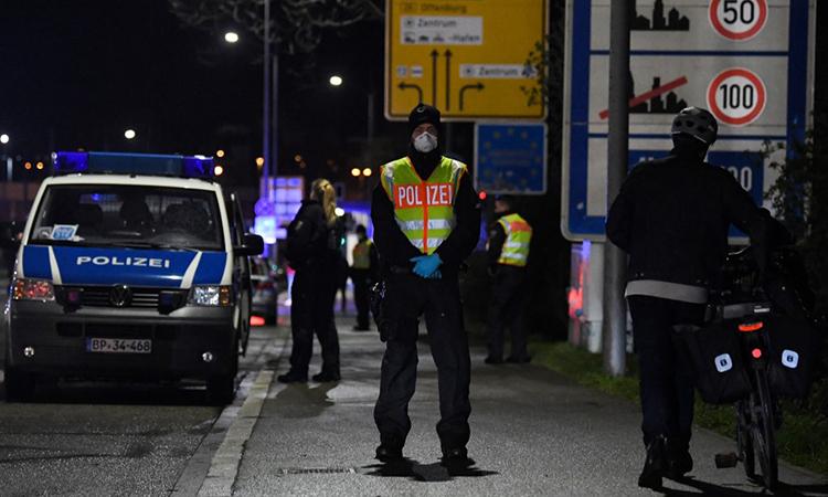 Một cảnh sát Đức đứng gách tại khu vực kiểm soát phương tiện giữa thành phố Kehl, Đức và Strasbourg, Pháp ngày 12/3. Ảnh: AFP.