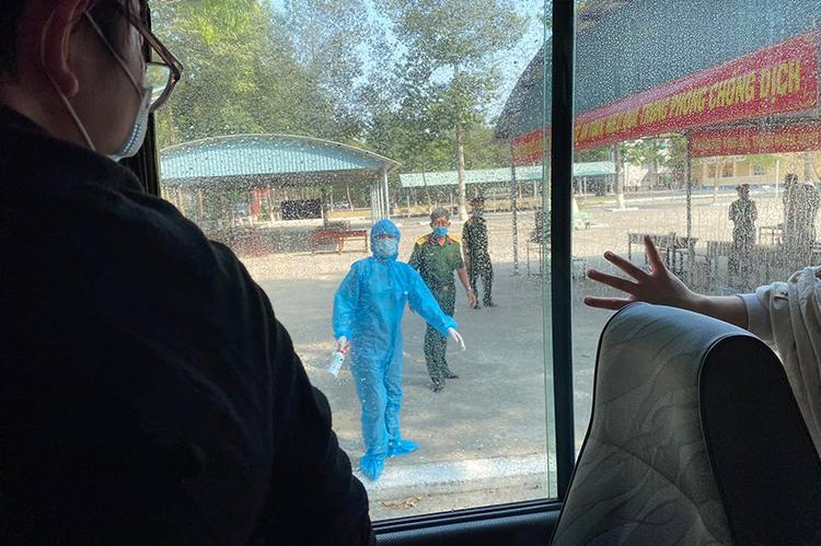 Xe đưa nhóm hành kháchvề từ châu Âu đếnkhu cách ly ở Trường quân sự Quân khu 7, TP HCM, chiều 16/3. Ảnh: Anh Tuấn.