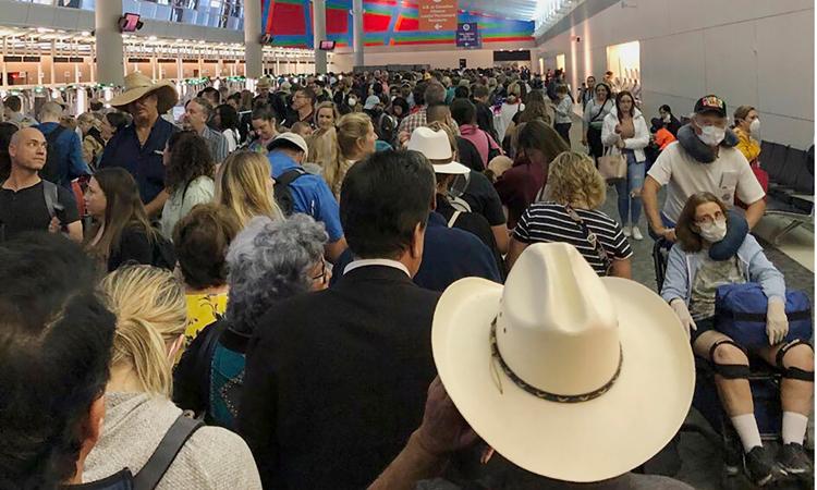 Hành khách chen chúc chờ đợi làm thủ tục ở sân bay quốc tế Fort Worth ở Dallas hôm 14/3. Ảnh: AP.