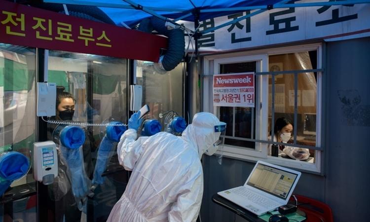 Y tá làm vi?c t?i m?t tr?m xét nghi?m ? bên ngoài b?nh vi?n Yangji ? Seoul ngày 17/3. ?nh: AFP.