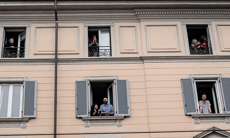 Ng??i dan c? v? ??i ng? y bác s? t? ban c?ng t?i Milan, Italy h?m 14/3. ?nh: NY Times.?