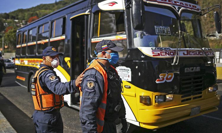 Vệ binh Quốc gia Venezuela đeo khẩu trang tham gia diễn tập phong tỏa đường vào thủ đô Caracas để ngăn Covid-19 ngày 15/3. Ảnh: AFP.