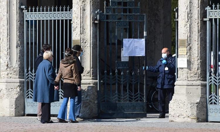 Nhân viên đóng cửa nghĩa trang Bergamo trong khi thân nhân của người quá cố đừng chờ bên ngoài. Ảnh: AFP.