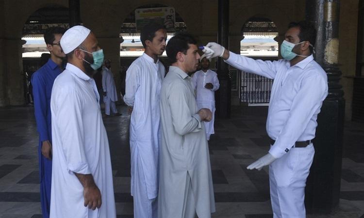 Quan chức y tế Pakistan kiểm tra thân nhiệt cho hành khách tại nhà ga thành phố Karachi hôm 16/3. Ảnh: AFP.