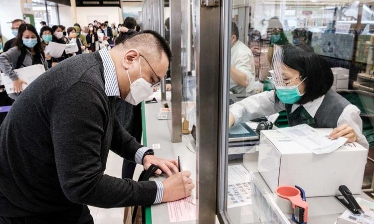 Một người gửi khẩu trang cho bố mẹ ở Canada tại bưu cực Hong Kong ngày 17/3. Ảnh: AFP.
