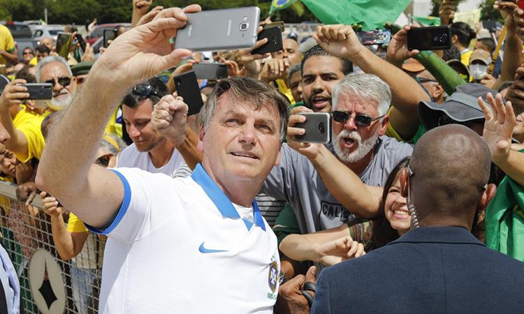 Tổng thống Brazil Jair Bolsonaro chụp ảnh selfie cùng người ủng hộ trong cuộc tuần hành ở thủ đô Brasilia ngày 15/3. Ảnh: AFP.