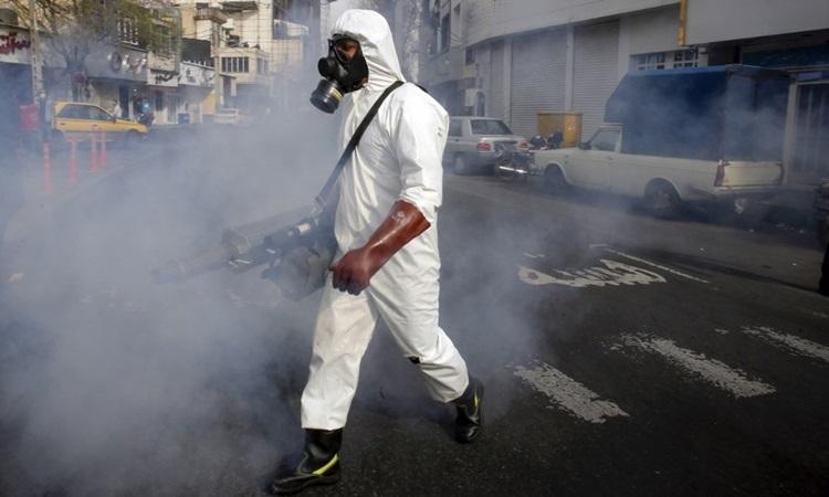 Lính cứu hỏa Iran khử trùng một con phố ở thủ đô Tehran để ngăn Covid-19 lây lan hôm 13/3. Ảnh: AFP.