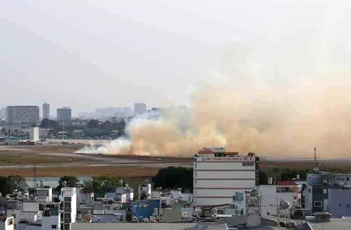 Đám cỏ khô gần đường băng cháy sau khi máy bay Airbus A321 nổ lốp, chiều nay. Ảnh: Anh Minh.