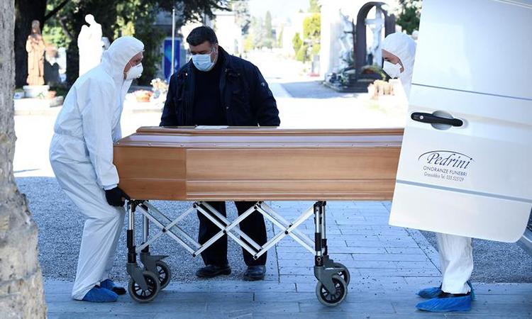 Người đàn ông đeo khẩu trang vận chuyển quan tài người chết vì Covid-19 đến nghĩa trangBergamo, Italy hôm 16/3.Ảnh: Reuters.