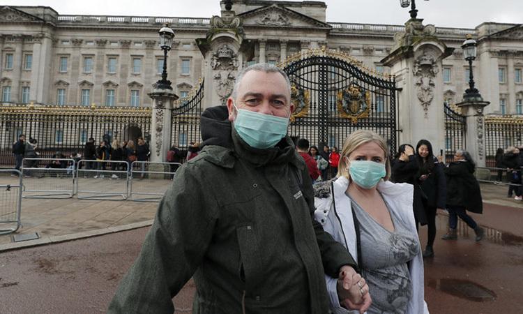 Cặp vợ chồng đeo khẩu trang đứng bên ngoài Cung điện Buckingham, London hôm 14/3. Ảnh: AP.