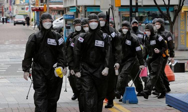 Quân đội Hàn Quốc đi khử trùng các tòa nhà tại thành phố Daegu hôm 15/3. Ảnh: Reuters.